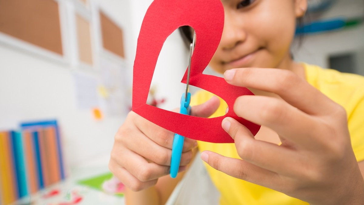 girl cutting out a heart with scissors.jpg